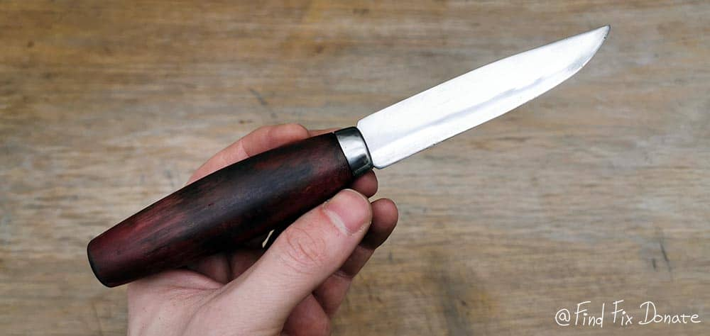 Hunting knife held in hand after restoration.