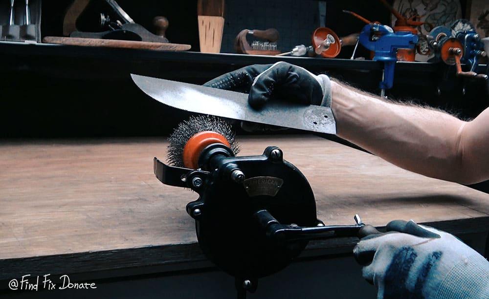 Steel brush on hand cranked grinder.