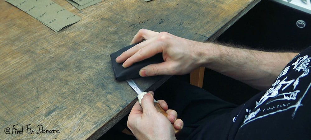 Sanding the old knife's blade with 120 grit sandpaper.