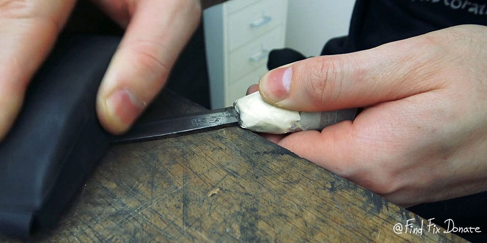 Sanding the old knife's blade with 400 grit sandpaper.