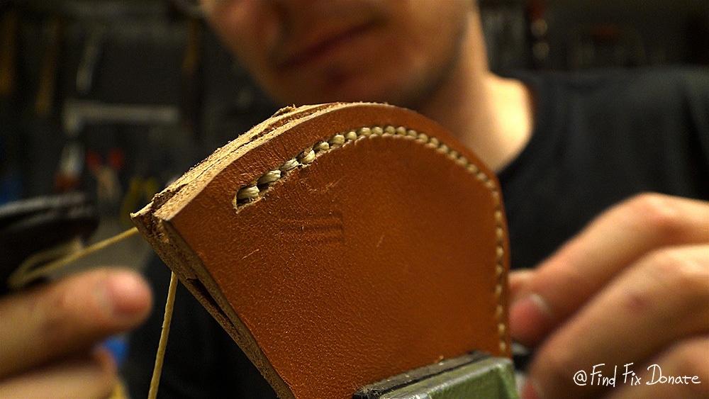 Finishing the stitching of leather sheath.