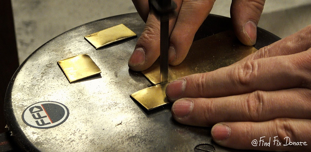 Cutting the brass on a treadle contour saw.